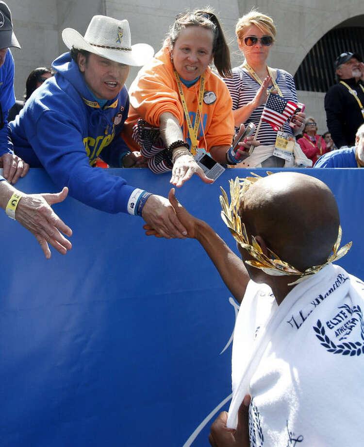 Boston Marathon bombings hero Carlos Arredondo congratulates Meb Keflezighi, right, who won the 118th Boston Marathon, Monday, April 21, 2014, in Boston. (AP Photo/Elise Amendola)
