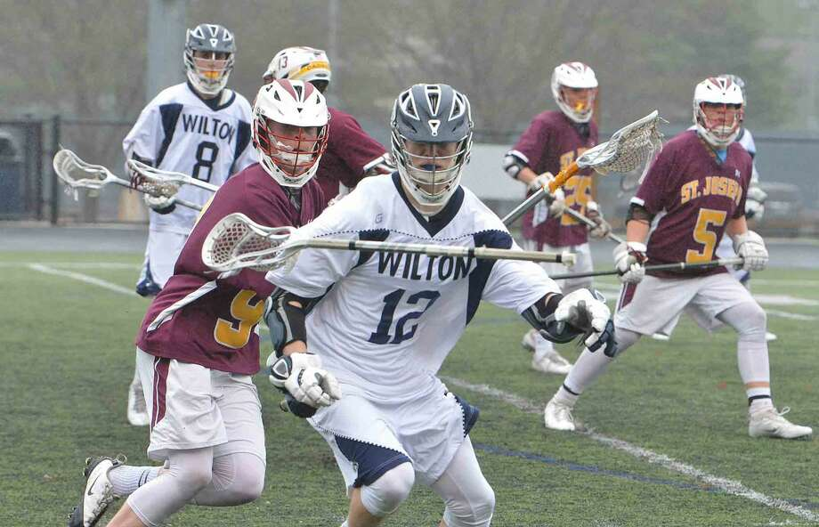 Wiltons #12 Zachary Zeyher loses his stick vs St Joes boys lacrosse at Wilton Conn. May 3 2016