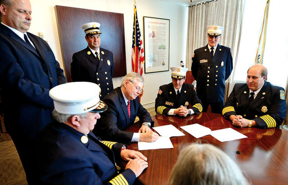 Hour photo / Erik Trautmann Mayor David Martin, Public Safety Director Ted Jankowski, Fire Chief Peter Brown, Turn Of River (TOR) Chief Frank Jacobellis, TOR Assistant Chief Matt Maounis, and TOR President Nicholas Jossem sign the agreement to consolidate the City and Turn of River Volunteer Fire Departments during a press conference Wednesday..