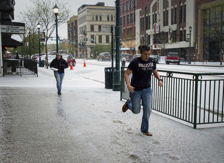 Pedestrians run through the hail in downtown Colorado Springs, Colo., Saturday, May 9, 2015, as another storm hits El Paso County. (Christian Murdock/The Gazette via AP)