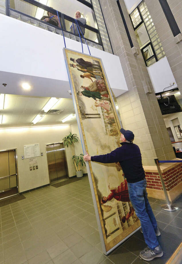 Bob Trimper and Scott Lee of Professional Hang Ups, top, remove the controversial mural, Steamboat Days on the Mississippi, from a second floor hallway at Norwalk City Hall May 5, 2016 in Norwalk, Conn. Norwalk Historical Commission director David Westmoreland oversaw the move and plans to hang the work in the Norwalk Museum next year as part of an exhibit.