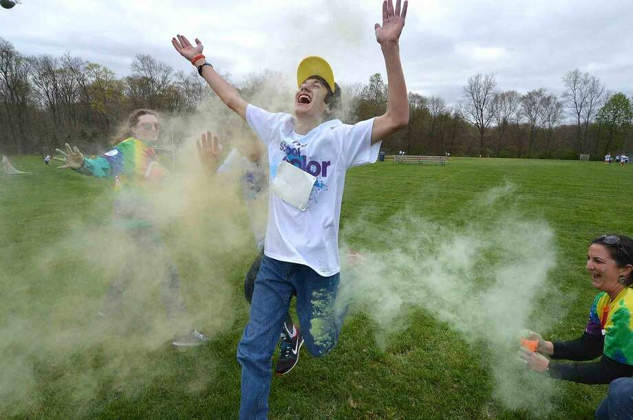 """8th grader Tyler Blaine jumps trough a blast of yellow during Wilton Youth Council's Youth to Youth club's new fundraising event called """"My School Color Run,"""" at Middlebrook School in Wilton, where participants walk/run a set course and get doused with spray color from Middlebrook staff during their run on Thursday May 5 2016 in Wilton Conn."""