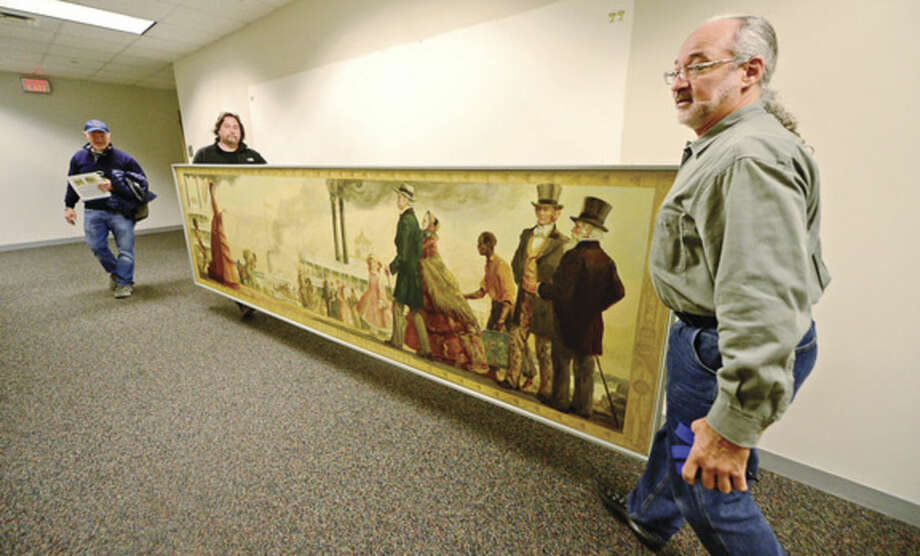 Bob Trimper and Scott Lee of Professional Hang Ups, remove the controversial mural, Steamboat Days on the Mississippi, from a second floor hallway at Norwalk City Hall May 5, 2016 in Norwalk, Conn. Norwalk Historical Commission Chairman David Westmoreland oversaw the move and plans to hang the work in the Norwalk Museum next year as part of an exhibit.