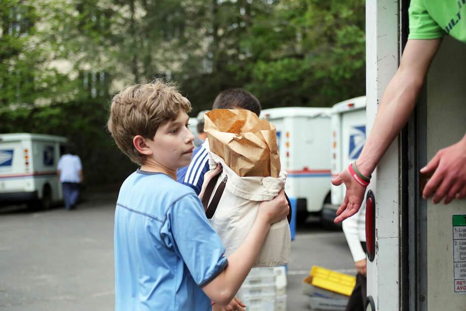 Matt Cressle loads food into the Person to Person truck at the Wilton Post Office for the National Association of Letter Carriers Food Drive Saturday afternoon. Hour Photo / Danielle Calloway