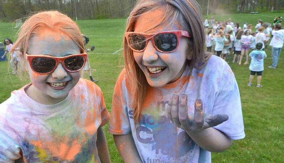 "At the finish line 6th graders Brokke Bohacs and Ashley Merkle are covered in orange during Wilton Youth Council's Youth to Youth club's new fundraising event called ""My School Color Run,"" at Middlebrook School in Wilton, where participants walk/run a set course and get doused with spray color from Middlebrook staff during their run on Thursday May 5 2016 in Wilton Conn."