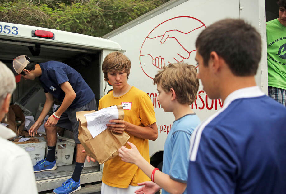 Trevor Johnson unloads food from a mail truck at the Wilton Post Office for the National Association of Letter Carriers Food Drive Saturday afternoon. Hour Photo / Danielle Calloway