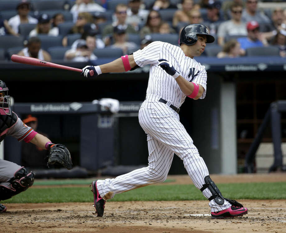 New York Yankees' Carlos Beltran, right, looks after his solo home run during the fourth inning of the baseball game against the Baltimore Orioles at Yankee Stadium, Sunday, May 10, 2015, in New York. (AP Photo/Seth Wenig)