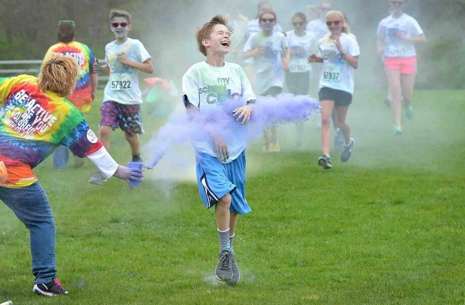 """7th grader Sam Rosen cant avoid the purple during Wilton Youth Council's Youth to Youth club's new fundraising event called """"My School Color Run,"""" at Middlebrook School in Wilton, where participants walk/run a set course and get doused with spray color from Middlebrook staff during their run on Thursday May 5 2016 in Wilton Conn."""