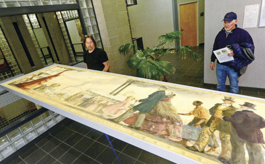 Scott Lee of Professional Hang Ups, removes the controversial mural, Steamboat Days on the Mississippi, from a second floor hallway at Norwalk City Hall May 5, 2016 in Norwalk, Conn. Norwalk Historical Commission director David Westmoreland oversaw the move and plans to hang the work in the Norwalk Museum next year as part of an exhibit.
