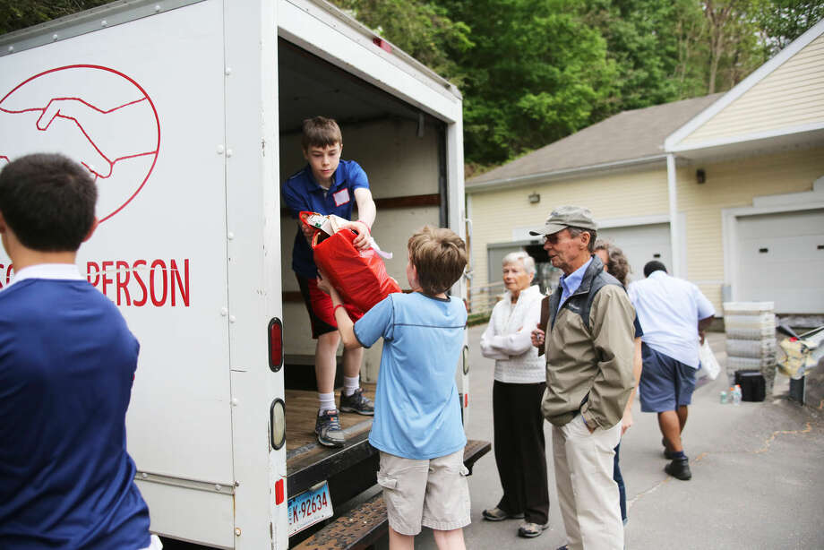 Michael Wallace loads food into the Person to Person truck at the Wilton Post Office for the National Association of Letter Carriers Food Drive Saturday afternoon. Hour Photo / Danielle Calloway