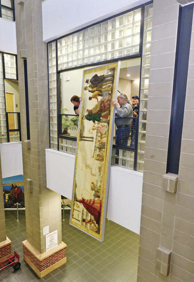 Bob Trimper and Scott Lee of Professional Hang Ups, remove the controversial mural, Steamboat Days on the Mississippi, from a second floor hallway at Norwalk City Hall May 5, 2016 in Norwalk, Conn. Norwalk Historical Commission director David Westmoreland oversaw the move and plans to hang the work in the Norwalk Museum next year as part of an exhibit.
