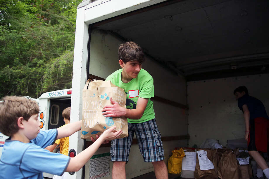 Nick Koleszar loads food into the Person to Person truck at the Wilton Post Office for the National Association of Letter Carriers Food Drive Saturday afternoon. Hour Photo / Danielle Calloway