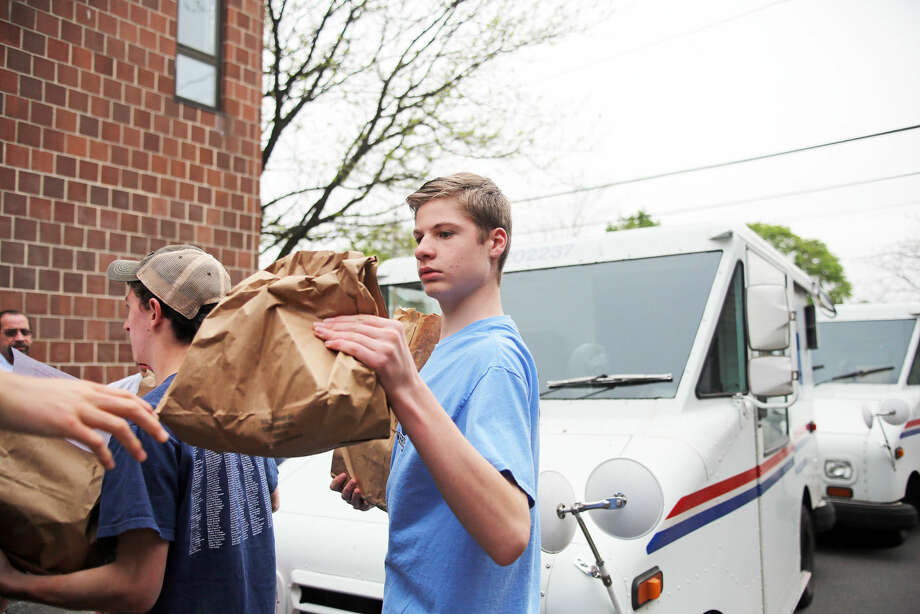 Riley Sexton unloads food from a mail truck at the South Norwalk Community Center for the National Association of Letter Carriers Food Drive Saturday afternoon. Hour Photo / Danielle Calloway