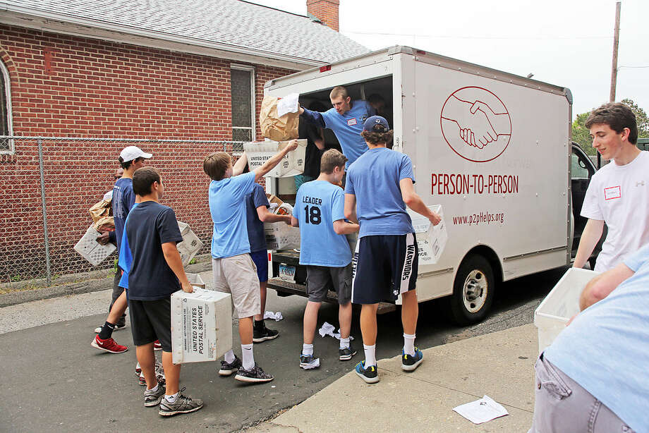 Food is unloaded from the Person to Person truck at the South Norwalk Community Center for the National Association of Letter Carriers Food Drive Saturday afternoon. Hour Photo / Danielle Calloway