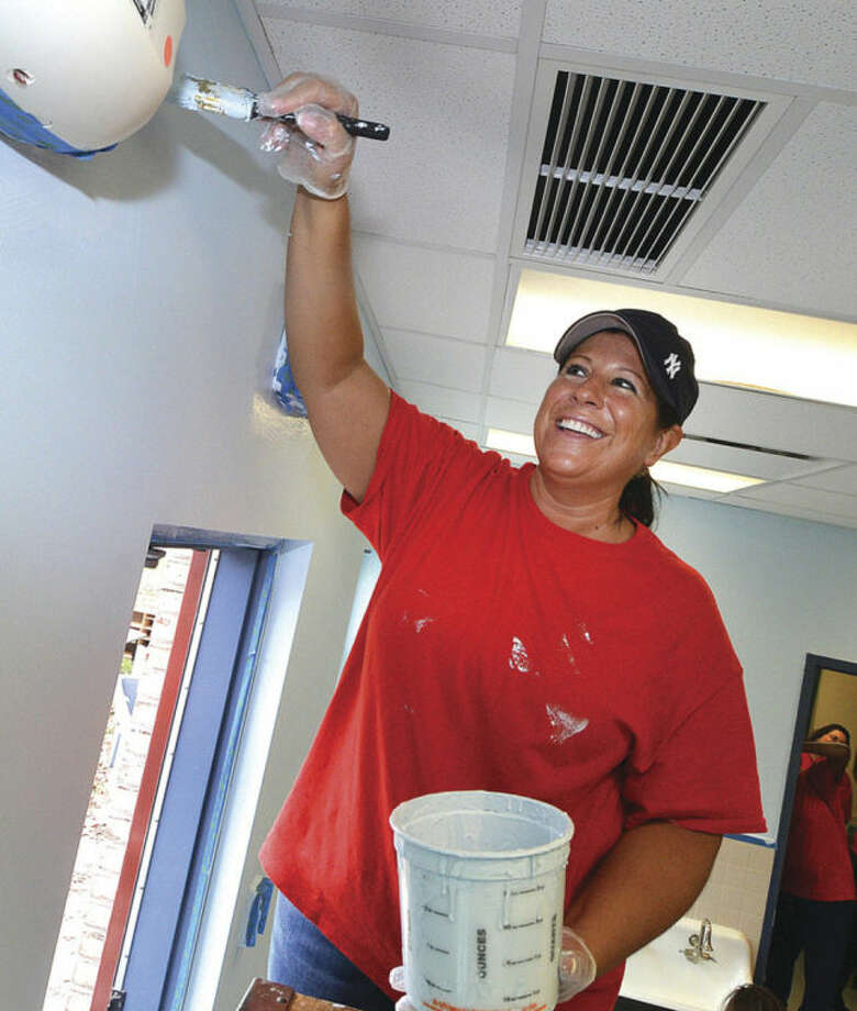 Hour Photo/Alex von Kleydorff. Karen Vida paints the trim near the ceiling in one of the classrooms at Nathaniel Ely School, part of more than 200 Pepperidge Farm employees that, painted cleaned and refurbrished the classrooms, ready for the return of students at the beginning of May
