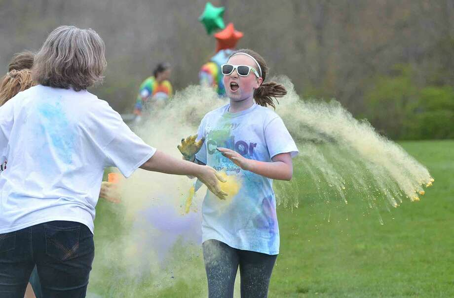 """Teacher Janet Nobles is ready with the yellow dust during Wilton Youth Council's Youth to Youth club's new fundraising event called """"My School Color Run,"""" at Middlebrook School in Wilton, where participants walk/run a set course and get doused with spray color from Middlebrook staff during their run on Thursday May 5 2016 in Wilton Conn."""