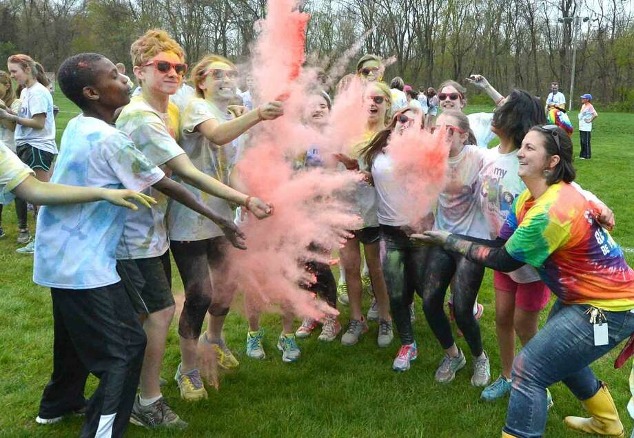 "Teacher Heather Heather schlitz celebrates the finish line with the students who spearheaded Wilton Youth Council's Youth to Youth club's new fundraising event called ""My School Color Run,"" at Middlebrook School in Wilton, where participants walk/run a set course and get doused with spray color from Middlebrook staff during their run on Thursday May 5 2016 in Wilton Conn."