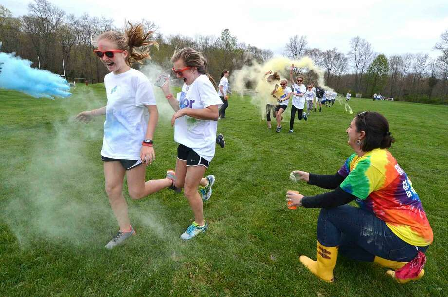 """Wilton Youth Council's Youth to Youth club's new fundraising event called """"My School Color Run,"""" at Middlebrook School in Wilton, where participants walk/run a set course and get doused with spray color from Middlebrook staff during their run on Thursday May 5 2016 in Wilton Conn."""