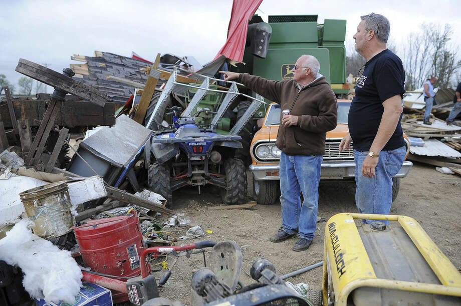 Mike Fechner, left, surveys damage to his property with Tim Asche, of American Family Insurance, on Sunday, May 10, 2015, near Delmont, S.D. The tornado hit the town southwest of Sioux Falls on Sunday morning, injuring nine people and damaging at least 20 buildings, including a century-old church. Two people remain hospitalized. Crews are working to restore water, electricity and phone service. (Joe Ahlquist/The Argus Leader via AP) NO SALES