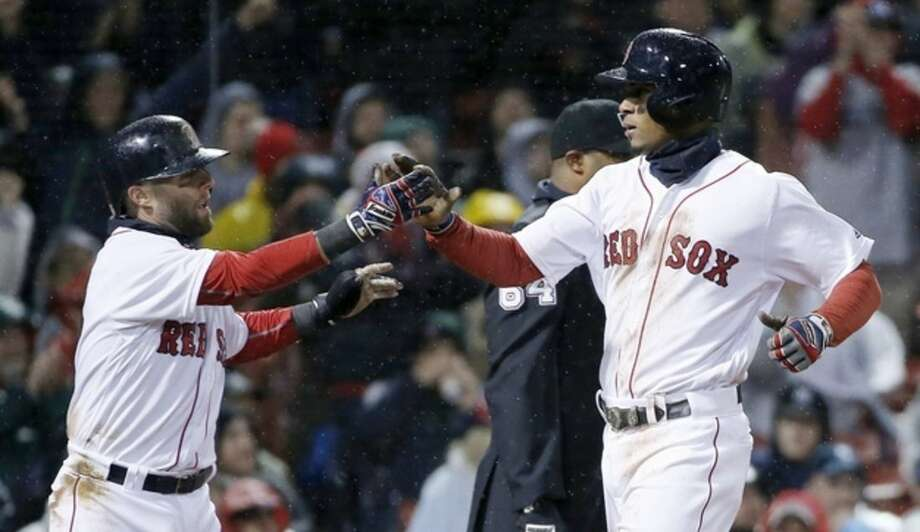 Boston Red Sox's Dustin Pedroia, left, and Xander Bogaerts celebrate after scoring on a two-run single by Hanley Ramirez during the third inning of a baseball game against the New York Yankees in Boston, Sunday, May 1, 2016. (AP Photo/Michael Dwyer)