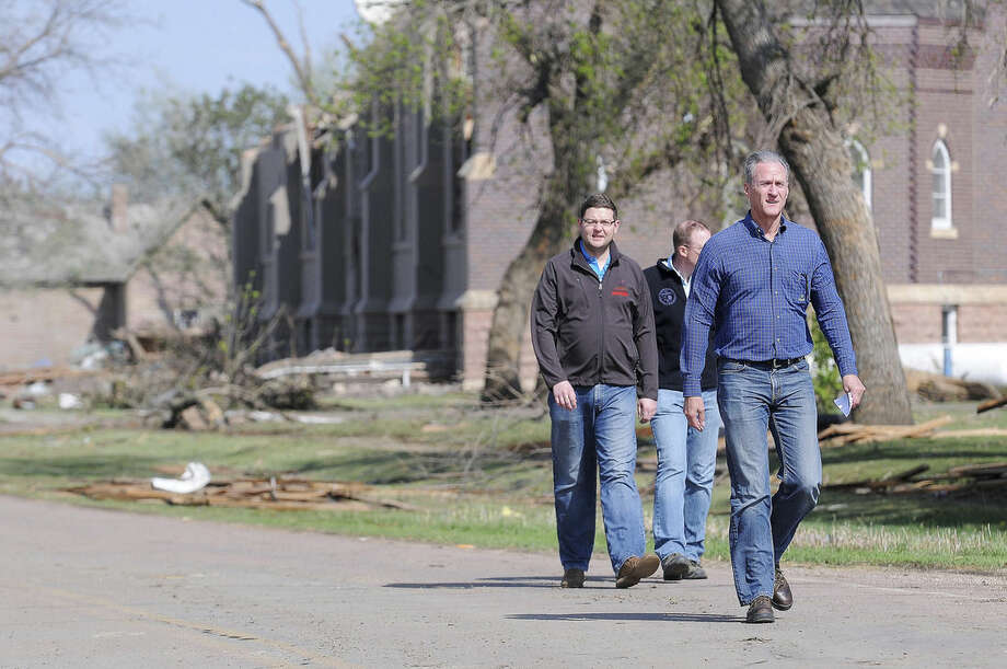 South Dakota Gov. Dennis Daugaard, right, walks down Main Street in Delmont, S.D., on Sunday, May 10, 2015, after a tornado tore through the area damaging homes and businesses on Sunday morning. The tornado injured at least nine people and damaging at least 20 buildings, including a century-old church. Crews are working to restore water, electricity and phone service. (Joe Ahlquist/The Argus Leader via AP) NO SALES