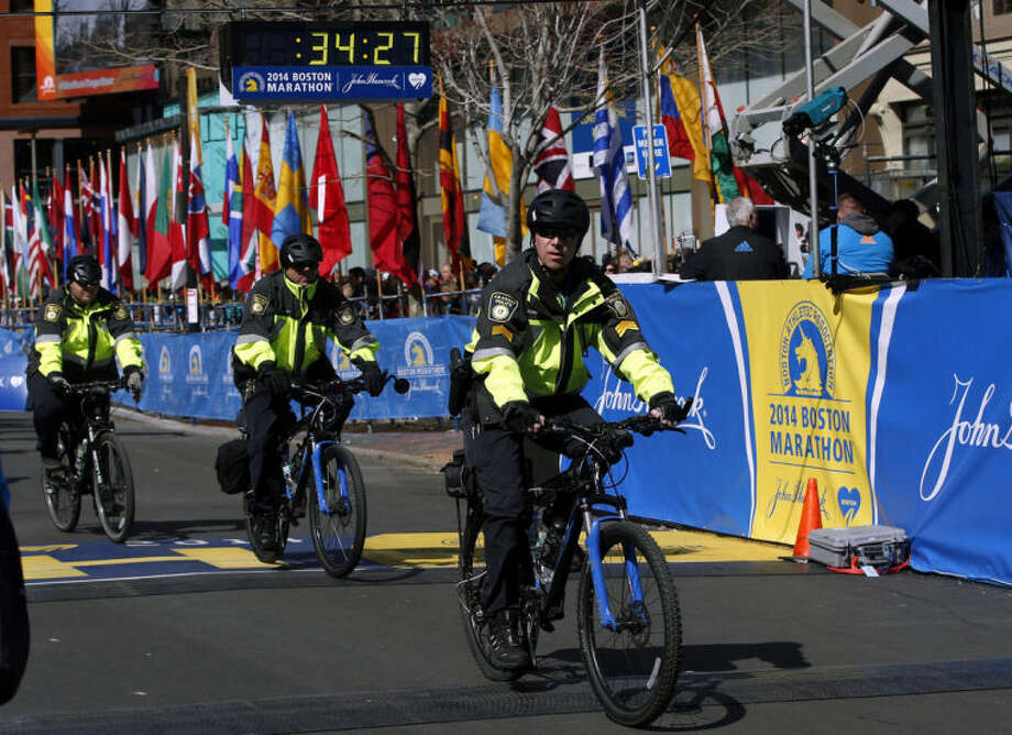 Boston Police officers on bicycles ride across the finish line before during 118th Boston Marathon Monday, April 21, 2014 in Boston. (AP Photo/Elise Amendola)