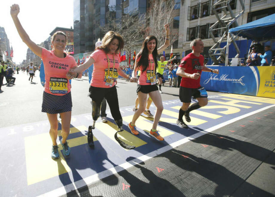 AP photo / Elise AmendolaDouble amputee Celeste Corcoran, center, a victim of last year's bombings, reaches the finish line of the 118th Boston Marathon Monday in Boston with the aid of her sister Carmen Acabbo, left, and daughter Sydney, right, who was also wounded last year.