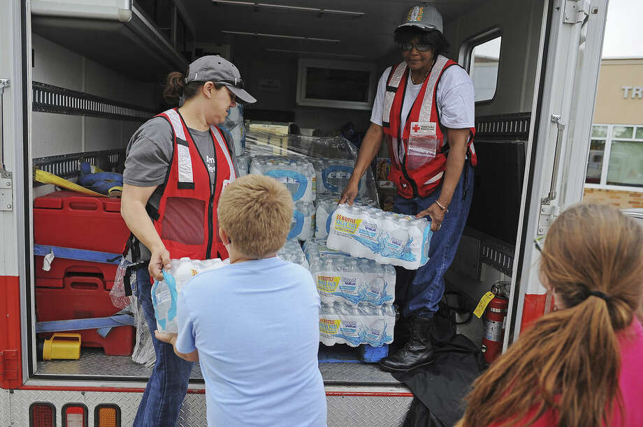Birgit Huwer, left, and Brindia Hall, both with the American Red Cross, hand out packs of water from an American Red Cross Disaster Relief vehicle on Sunday, May 10, 2015, outside the Tripp-Delmont School in Tripp, S.D. The tornado hit the town of Delmont, southwest of Sioux Falls on Sunday morning, injuring nine people and damaging at least 20 buildings, including a century-old church. Two people remain hospitalized. Crews are working to restore water, electricity and phone service. (Joe Ahlquist/The Argus Leader via AP) NO SALES