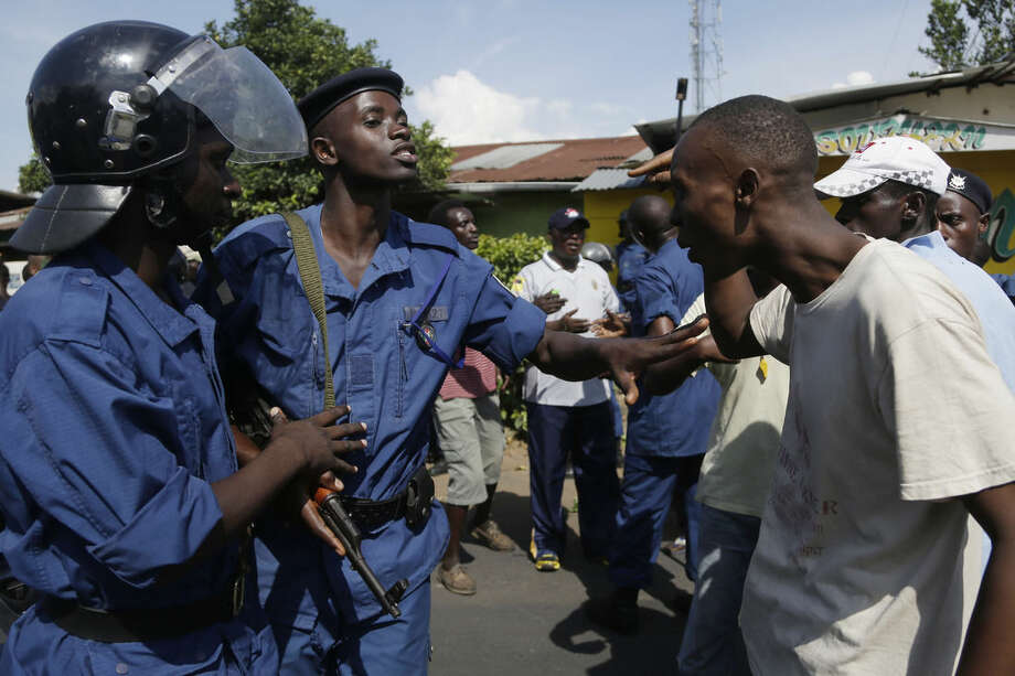 A demonstrator argues with police protesters march through the Musaga district of Bujumbura, in Burundi, Monday, May 11, 2015. Police and army negotiated with over 2000 protesters to allow delivery trucks to enter the city. One person was killed in a clash with Burundi's police on Sunday in demonstrations in the capital, Bujumbura, as the government ordered a ban on any further street protests over President Pierre Nkurunziza's bid for a third term in power. (AP Photo/Jerome Delay)