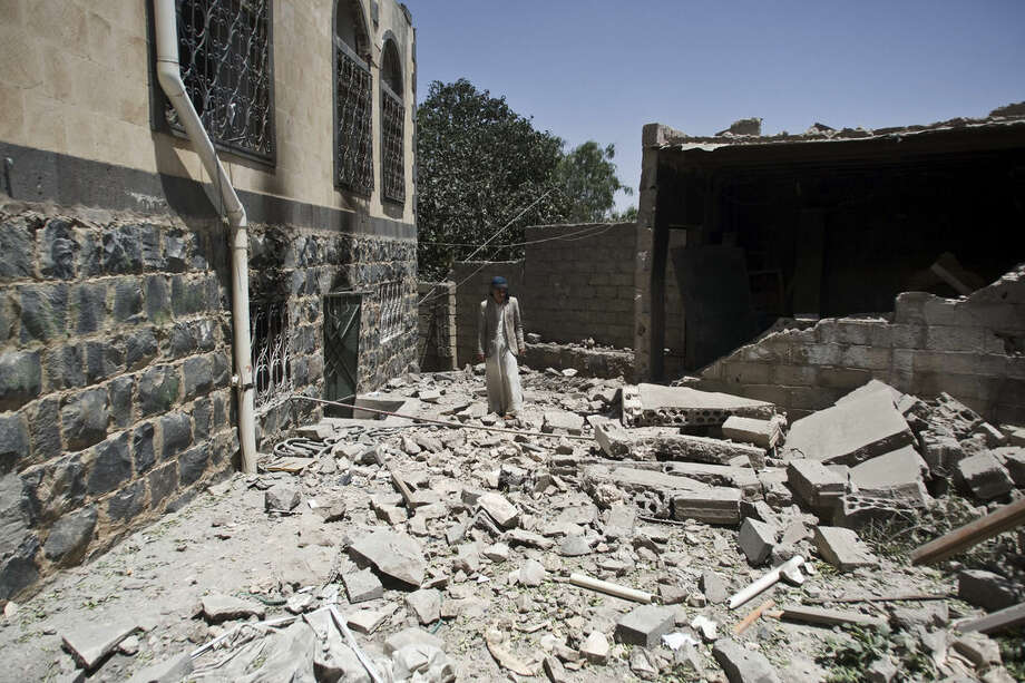 A Shiite rebel known as a Houthi inspects his house destroyed by a Saudi-led airstrike in Sanaa, Yemen, Monday, May 11, 2015. The raging conflict in Yemen has killed over 1,400 people, many of them civilians, since March 19, according to the United Nations. (AP Photo/Hani Mohammed)