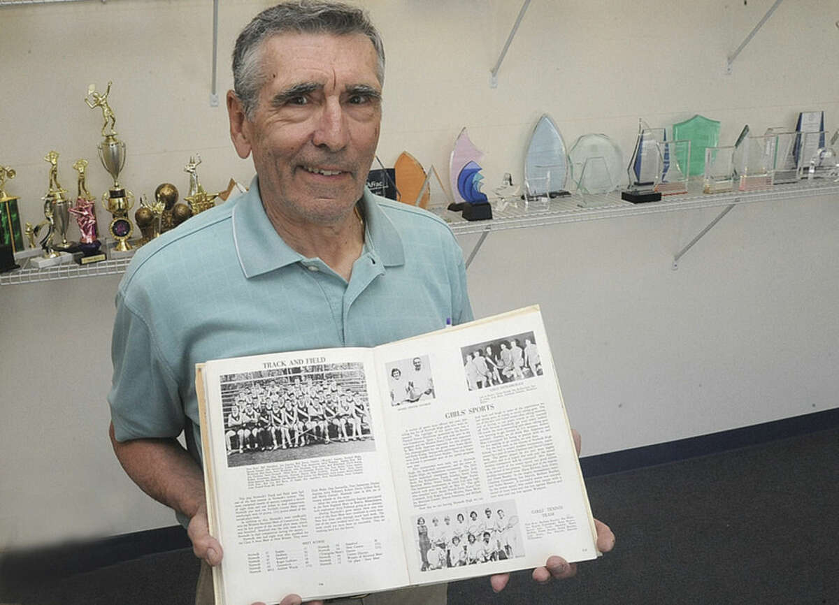 Hour photo/Matthew Vinci Danny Santarella displays a yearbook picture of the 1959 Norwalk High School track team, which he helped lead to the County Conference crown.