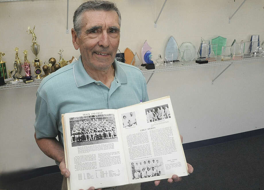 Hour photo/Matthew VinciDanny Santarella displays a yearbook picture of the 1959 Norwalk High School track team, which he helped lead to the County Conference crown.
