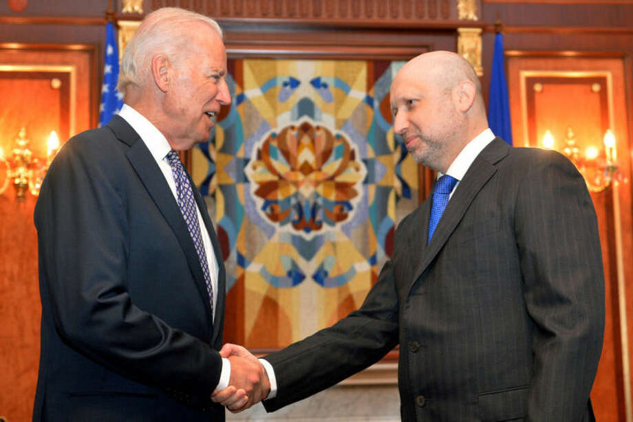 U.S. Vice President Joe Biden, left, is greeted by Oleksandr Turchynov, the acting Ukrainian prime minister and president, Tuesday, April 22, 21014 in Kiev. Biden's visit to Ukraine comes at a crucial time, days after an international agreement was reached aimed at quelling violence in Ukraine. (AP Photo/Sergei Supinsky, Pool)