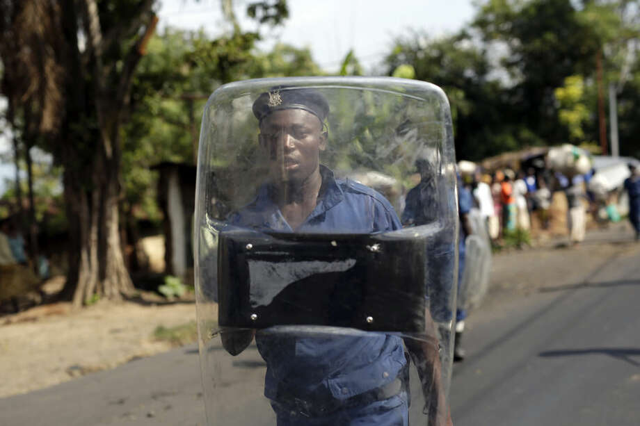 A police man patrols as protesters march through the Musaga district of Bujumbura, in Burundi, Monday, May 11, 2015. Police and army negotiated with over 2000 protesters to allow delivery trucks to enter the city. One person was killed in a clash with Burundi's police on Sunday in demonstrations in the capital, Bujumbura, as the government ordered a ban on any further street protests over President Pierre Nkurunziza's bid for a third term in power. (AP Photo/Jerome Delay)
