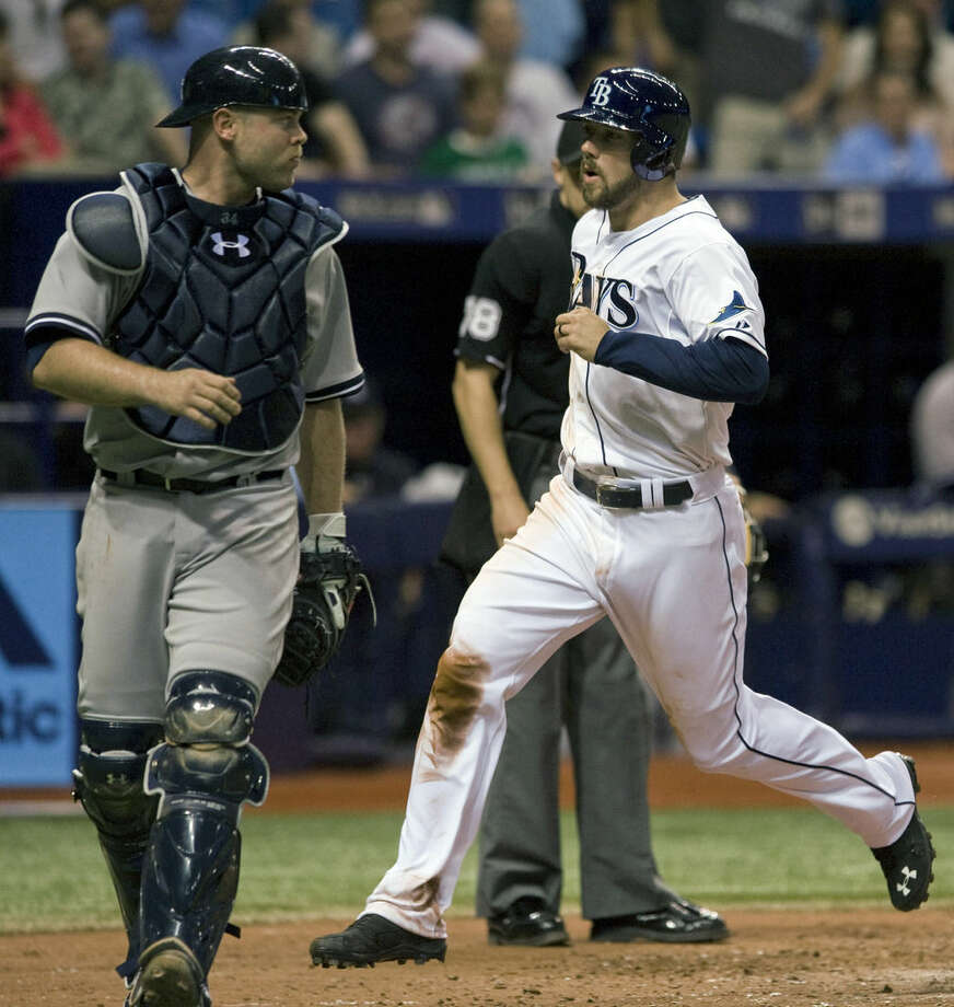 Tampa Bay Rays' Steve Souza Jr. scores past New York Yankees catcher Brian McCann, left, on a wild pitch from New York reliever Dellin Betances during the eighth inning of a baseball game Tuesday, May 12, 2015, in St. Petersburg, Fla. The Rays beat the Yankees 4-2. (AP Photo/Steve Nesius)