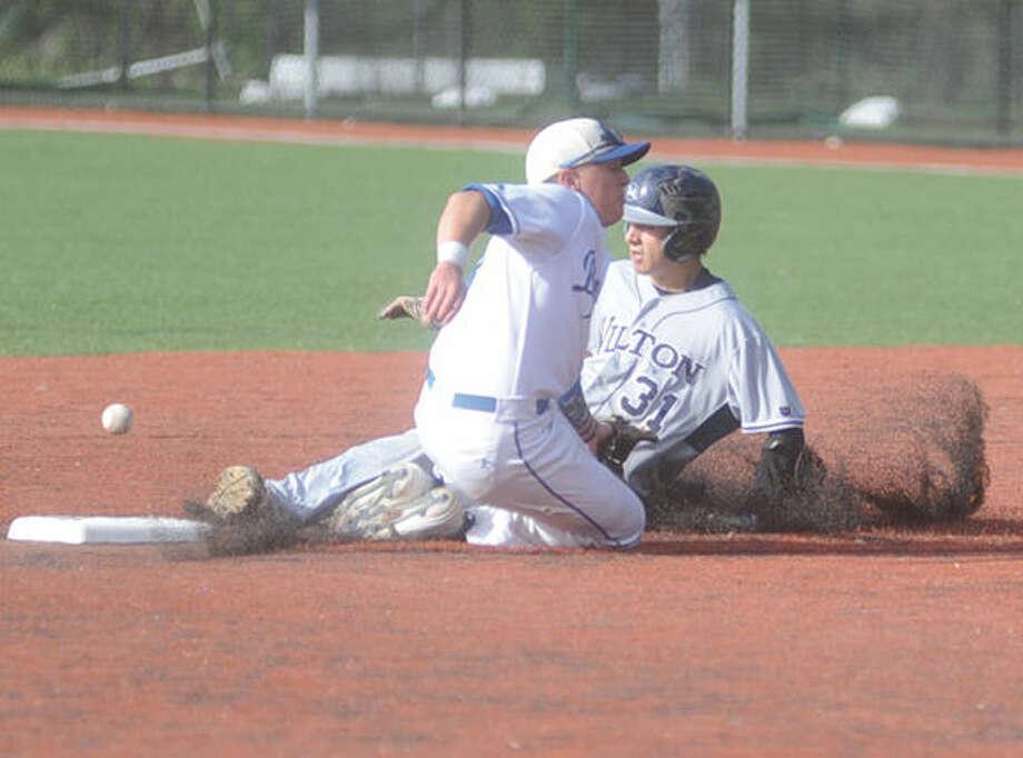 Wilton's Dillon Lifrieri slides in safe, the ball gets away from Darien shortstop Jake Frasca. Hour photo/Matthew Vinci