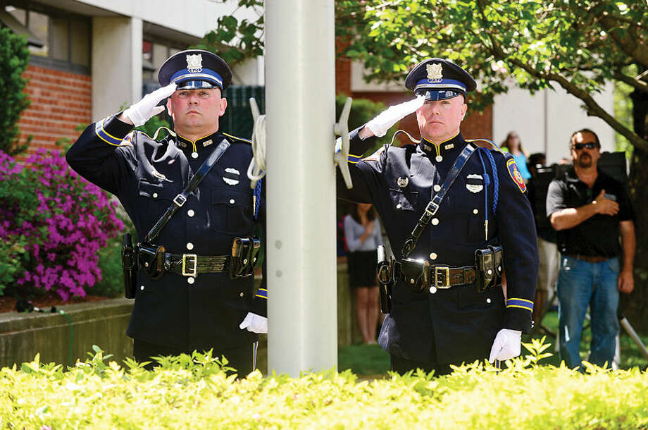 Hour photo / Erik Trautmann Officers Ryan McAllister and Chris Brown raise the flag to half mast as The Stamford Police Department holds their annual memorial service Wednesday morning to honor those officers who died in the line of duty.