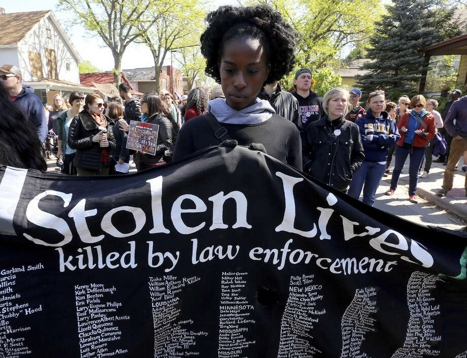 James Madison Memorial High School student Naomi Makesa, 17, helps hold a banner during a rally for Tony Robinson along Williamson Street in Madison, Wis., Wednesday, May 13, 2015. Dane County District Attorney Ismael Ozanne said Tuesday, May 12, that he wouldn't file charges against Madison Officer Matt Kenny in the March 6 death of Robinson, saying the officer used lawful deadly force after he was staggered by a punch to the head and feared for his life. (John Hart/Wisconsin State Journal via AP)