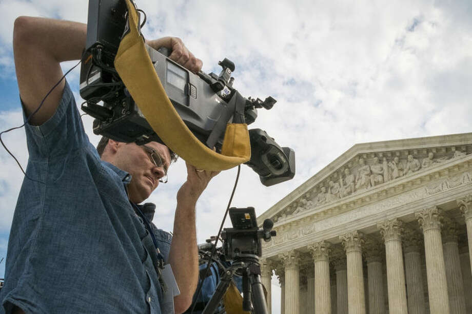 A videojournalist sets up outside of the Supreme Court in Washington, Tuesday, April 22, 2104. The court is hearing oral arguments between Aereo, Inc., an Internet startup company that gives subscribers access to television on their laptops and other portable devices and the over-the-air broadcasters. (AP Photo/J. David Ake)