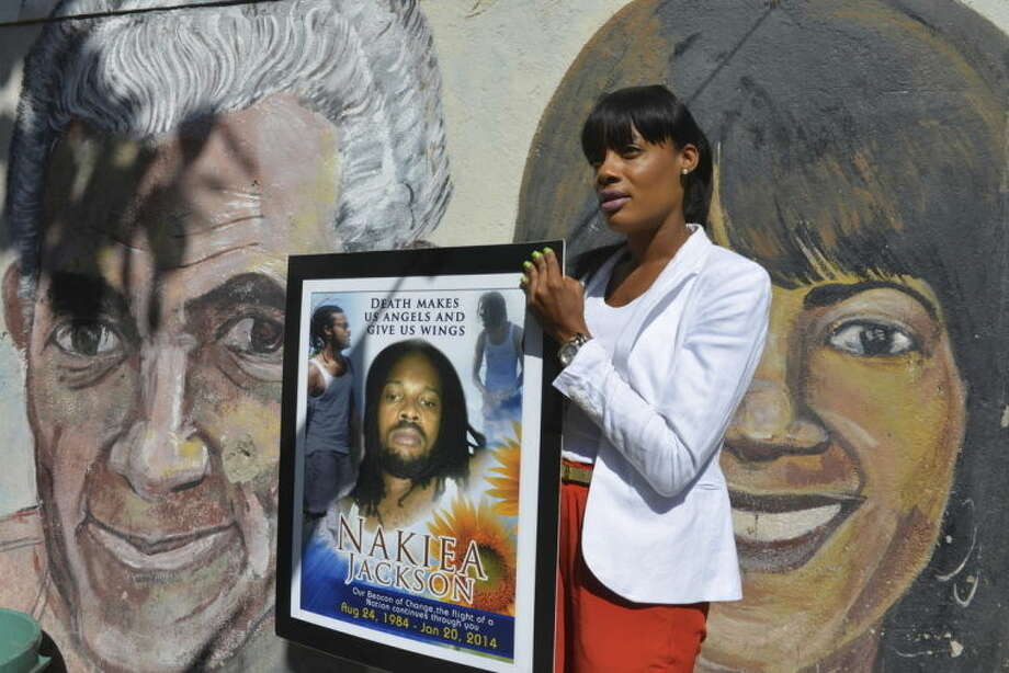 """In this April 16, 2014, photo, Shackelia Jackson-Thomas holds a poster showing her brother, Nakiea Jackson, just outside his small """"cookshop"""" in the Orange Villa section of Jamaica's capital of Kingston. Earlier this year, the 27-year-old cook was shot dead by a policeman as pots of curried goat simmered on the stove of his kitchen, the exterior of which is decorated with murals of past and present political leaders. The patrolman who shot him is one of 27 police officers now facing charges of murder brought by an investigative commission probing allegations against police and soldiers. Jamaica's security forces have long been accused of indiscriminate shootings and unlawful killings. (AP Photo/David McFadden)"""