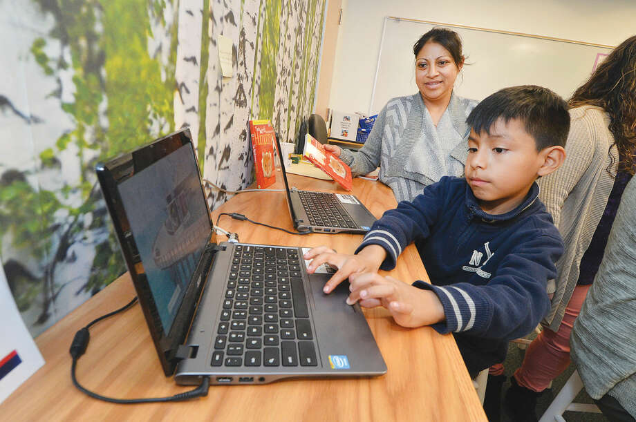 Third-grader Jayden Criollo with his mom Rosa works on a computer in The Family Center at Brookside School on Thursday April 28 2016 in Norwalk Conn.
