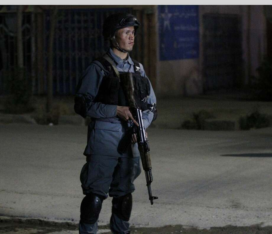 An Afghan policeman stands guard by the Park Palace Hotel after an attack by Taliban militants, in Kabul, Afghanistan, Wednesday, May 13, 2015. Gunmen have stormed a guesthouse in the Afghan capital used by both foreigners and locals, sparking a gun battle with police The attackers targeted Kabul's Park Palace Hotel on Wednesday night Kabul police chief Gen. Abdul Rahman Rahimi says the gunmen were still shooting at his officers. (AP Photo/Allauddin Khan)