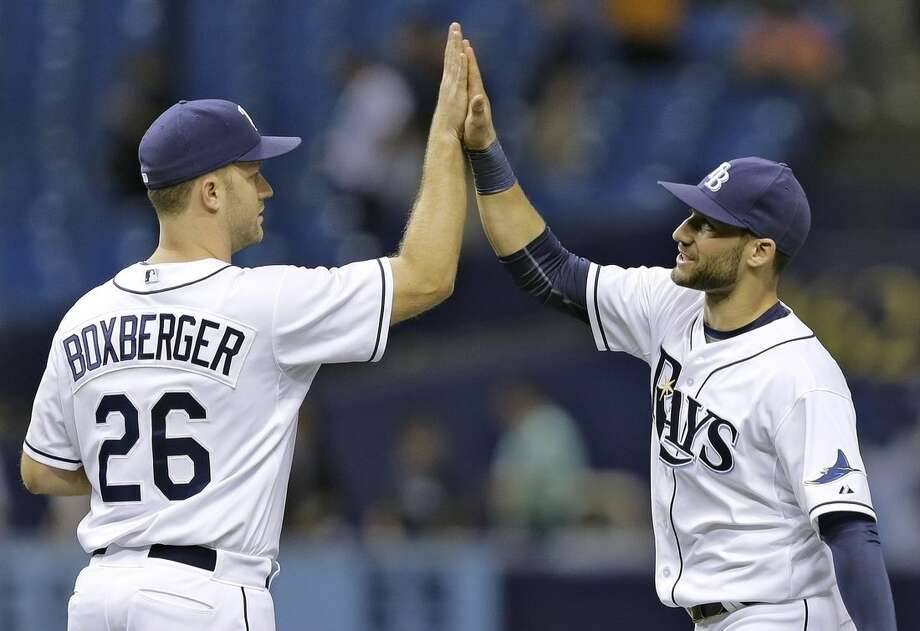 Tampa Bay Rays center fielder Kevin Kiermaier, right, high fives relief pitcher Brad Boxberger after the closing out the New York Yankees during the ninth inning of a baseball game Wednesday, May 13, 2015, in St. Petersburg, Fla. The Rays defeated the Yankees 3-2. (AP Photo/Chris O'Meara)