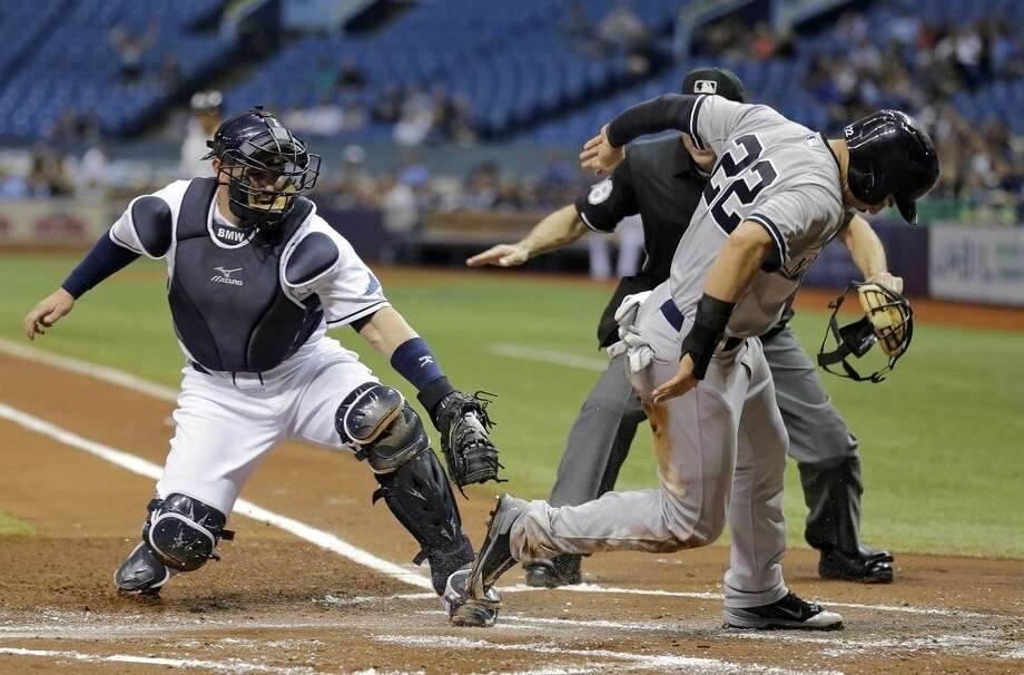 New York Yankees' Jacoby Ellsbury (22) scores ahead of the tag by Tampa Bay Rays catcher Bobby Wilson on an RBI single by Mark Teixeira during the first inning of a baseball game Wednesday, May 13, 2015, in St. Petersburg, Fla. (AP Photo/Chris O'Meara)
