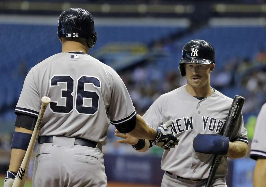 New York Yankees' Brett Gardner shakes hands with on-deck batter Carlos Beltran after scoring on a single by Brian McCann off Tampa Bay Rays starting pitcher Nathan Karns during the first inning of a baseball game Wednesday, May 13, 2015, in St. Petersburg, Fla. (AP Photo/Chris O'Meara)