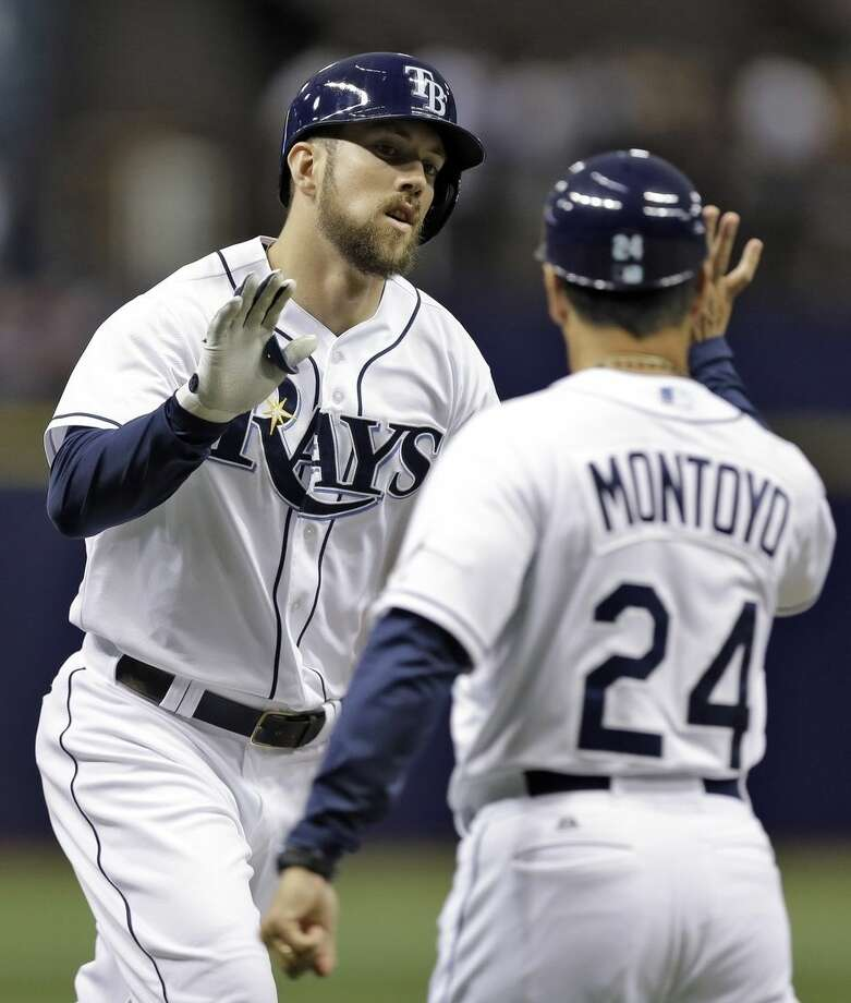 Tampa Bay Rays' Steven Souza Jr. high fives third base coach Charlie Montoyo (24) after his home run off New York Yankees starting pitcher Adam Warren during the first inning of a baseball game Wednesday, May 13, 2015, in St. Petersburg, Fla. (AP Photo/Chris O'Meara)