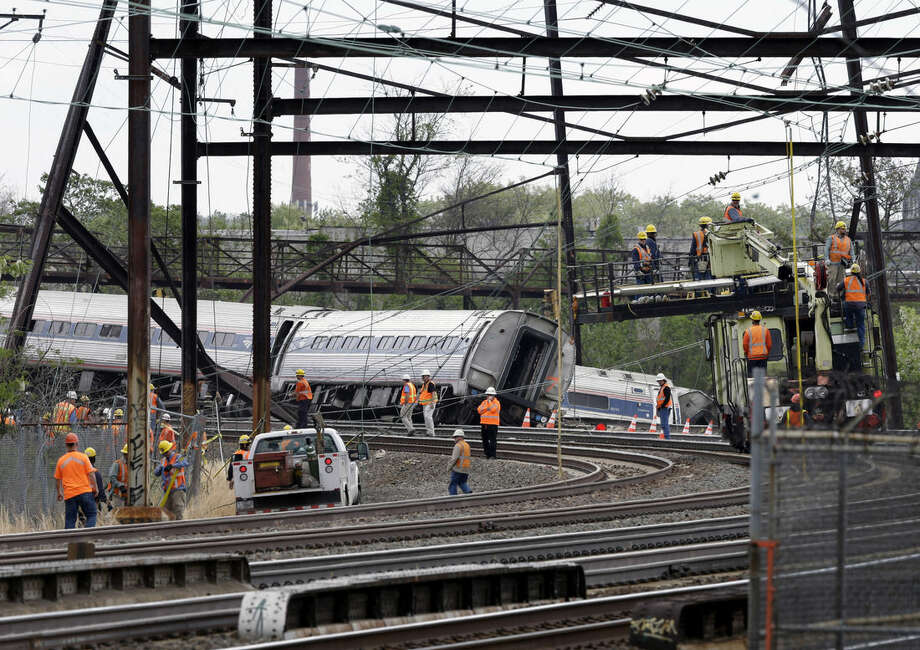 Emergency personnel walk near the scene of a deadly train wreck, Wednesday, May 13, 2015, in Philadelphia. Federal investigators arrived Wednesday to determine why an Amtrak train jumped the tracks in Tuesday night's fatal accident. (AP Photo/Mel Evans)