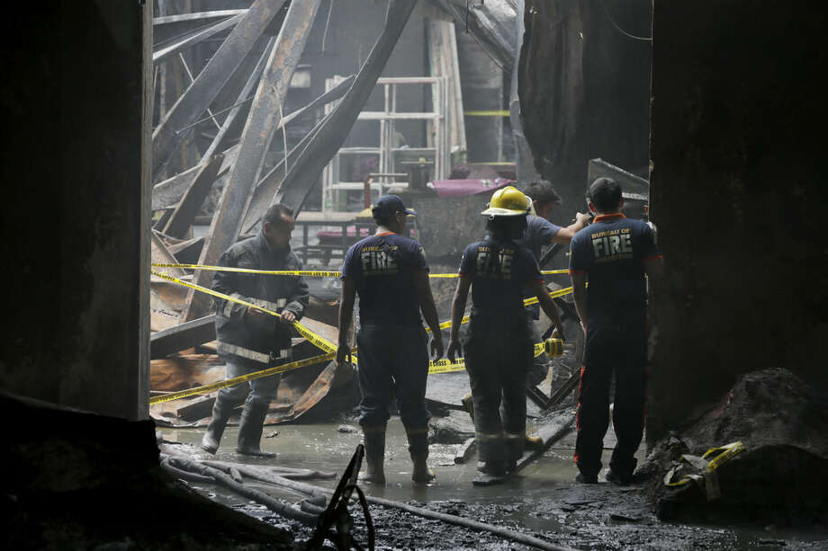 Firemen secure with yellow tape the burnt Kentex rubber slipper factory in Valenzuela city, a northern suburb of Manila, Philippines, Thursday, May 14, 2015. On Thursday, police will open a criminal investigation into the incident that killed dozens of people, as a relative of several of the victims said the blaze had trapped workers in the building's second floor where iron grills on windows prevented their escape. (AP Photo/Bullit Marquez)