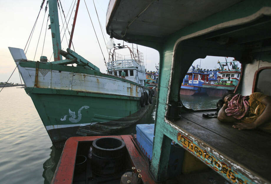 A fisherman sleeps on his boat as the vessel, left, used to carry Rohingya Muslims from Myanmar and migrants from Bangladesh is docked at a port in Lhokseumawe, Aceh province, Indonesia, Thursday, May 14, 2015. More than 1,600 migrants and refugees have landed on the shores of Malaysia and Indonesia in the past week and thousands more are believed to have been abandoned at sea, floating on boats with little or no food after traffickers literally jumped ship fearing a crackdown. (AP Photo/Binsar Bakkara)