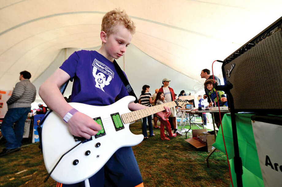 Hour photo / Erik Trautmann Luke Lileika plays guitar through a Rullywear effecs box at the annual Mini Makers Faire at the Jessup Green in Westport Saturday.